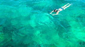 Aerial top view of woman snorkeling from above, girl snorkeler swimming in a clear tropical sea water with corals royalty free stock photography