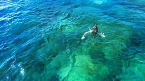Aerial top view of woman snorkeling from above, girl snorkeler swimming in a clear tropical sea water with corals. During summer vacation in Thailand royalty free stock images