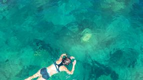 Aerial top view of woman snorkeling from above, girl snorkeler swimming in a clear tropical sea water with corals. During summer vacation in Thailand stock photos