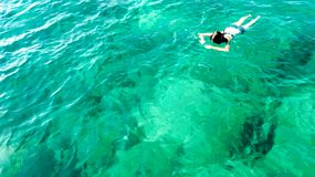 Aerial top view of woman snorkeling from above, girl snorkeler swimming in a clear tropical sea water with corals royalty free stock image