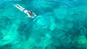 Aerial top view of woman snorkeling from above, girl snorkeler swimming in a clear tropical sea water with corals stock photos