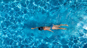 Aerial top view of woman in swimming pool water from above, tropical vacation Stock Photo