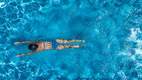 Aerial top view of woman in swimming pool water from above, tropical vacation concept Royalty Free Stock Photo