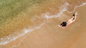 Aerial top view of young woman in bikini relaxing on sand tropical beach by sea and waves from above, girl on island beach. Aerial top view of young woman in royalty free stock photos