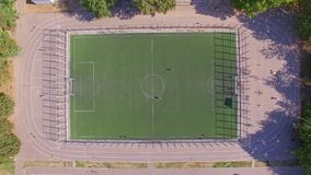 Aerial topside down view of football field with amateur football players. Aerial top down view of football field with two amateur football players training stock video footage
