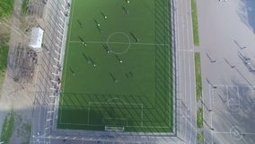 Aerial view of school football field with amateur football players. Aerial topside down view of school football field with amateur football players stock video footage