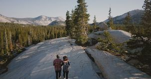 Aerial tracking shot of young romantic couple hugging, hiking together on amazing white rock at Yosemite park forest. Newlywed man and woman enjoying traveling stock video footage