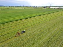 Aerial of tractor with harrow in field Stock Image