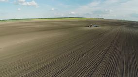 Aerial of tractor on harvest field top view from height stock video footage