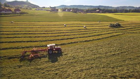 Aerial of tractor makes hay bales and drops them covered in plastic on sunny day in the mountains stock video footage