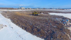 Aerial: tractor working at the garbage dump. Landfill, garbage dump, trash dump from above. 4K stock footage