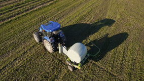 Aerial: Tractor wrapping a bale of hay after collecting the dried hay on a field stock footage