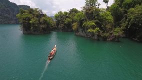 Aerial: Traditional Thai Long Tail Boat Sailing with Tourists at Cheow Lan Lake. Surat Thani Province, Thailand. HD. Aerial: Traditional Thai Long Tail Boat stock video footage
