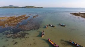Aerial: traditional thai long-tail boats in low tide water on the Rawai beach. HD birds-eye view. Phuket, Thailand stock footage
