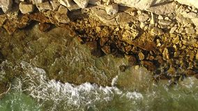 Aerial. Transparent waves on the stone banks of the sunny Algarve. Portugal stock video footage