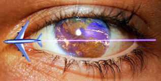 Aerial transport. Close view to an eye from  which cornea is the Earth with the American continent, and a passengers plane crossing the image over it Stock Photography