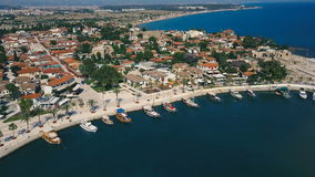 Aerial travel video view of old city with yacht and boats at marina in front of it. Waterfront, ocean river marina port. Aerial drone travel video view of old stock footage