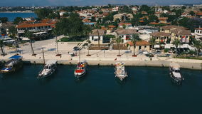 Aerial travel video view of old city with yacht and boats at marina in front of it. Waterfront, ocean river marina port. Aerial drone travel video view of old stock video