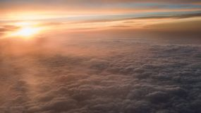 Aerial traveling. Flying at dusk or dawn. Fly through orange cloud and sun royalty free stock photography