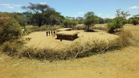 Aerial of a tribal hut in African rift valley with thorny fence in vast savannah