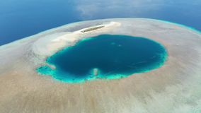 Aerial: tropical atoll view from above, blue lagoon turquoise water coral reef, Wakatobi Marine National Park, Indonesia - concept stock footage