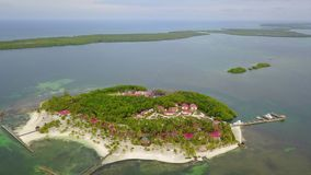 Aerial of Tropical Island Resort in Belize. Aerial view of a gorgeous resort on a small, remote island in Turneffe Atoll, Belize. The area supports a wide stock video footage