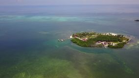 Aerial of Tropical Island Resort in Belize. Aerial view of a gorgeous resort on a small, remote island in Turneffe Atoll, Belize. The area supports a wide stock video