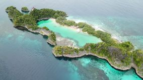 Aerial of Tropical Limestone Island in Indonesia. A beautiful tropical island in Raja Ampat, Indonesia, is surrounded by coral reef and calm seas. This unique stock footage