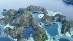 Aerial of Tropical, Limestone Islands in Raja Ampat. The stunning limestone islands found in Raja Ampat are surrounded by healthy coral reefs. This beautiful stock footage