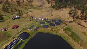 Aerial trout farm. Three aerial shots of a trout farm in some forest in mexico, water tanks in the middle of the forest used to bread trouts stock footage