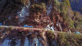 Aerial of trucks driving on the main road of East Bhutan. Three blue trucks driving on the road stock video footage