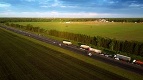 Aerial trucks stand in traffic jam on country highway. Aerial panorama trucks stand in traffic jam due to auto accident on highway against forest and fields at stock video