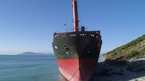 Aerial for tug boat moored on the ocean shore near the hill with green trees on blue sky background. Shot. Red