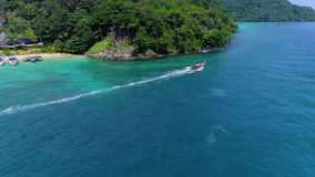 Aerial: Two boats leave from the Phi Phi Don beach. Thailand. Phi Phi Islands stock footage