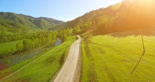 Aerial UHD 4K view. Low air flight over mountain rural dirt road and meadow at sunny summer morning stock footage