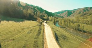 Aerial UHD 4K view. Low air flight over mountain rural dirt road and meadow at sunny summer morning stock video