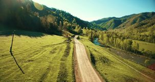 Aerial UHD 4K view. Low air flight over mountain rural dirt road and meadow at sunny summer stock video