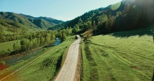 Aerial UHD 4K view. Low air flight over mountain rural dirt road and meadow at sunny stock video