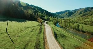 Aerial UHD 4K view. Low air flight over mountain rural dirt road and meadow at sunny summer morning. stock footage