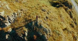 Orbital radial flight around young hiking man standing on top of the cliff. Hands up, winner!. Aerial UHD 4K view. Orbital radial flight around young hiking man stock footage