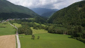 AERIAL: Valley among the hills with various types of fields and a car road stock video footage