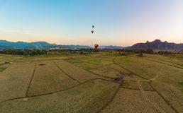 Aerial: Vang Vieng backpacker travel destination in Laos, Asia. Sunset over scenic cliffs and rock pinnacles, rice paddies valley royalty free stock photo
