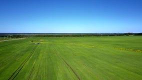 Aerial vast agro field landscape under blue sky. Beautiful aerial panorama vast green agro field landscape with distant tractor under blue sky stock footage