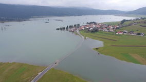 AERIAL: Vehicle trying to cross the flooded road stock video