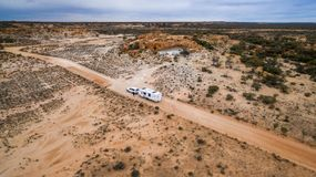 Aerial veiw of four wheel drive vehicle and large caravan on an road. Aerial veiw of four wheel drive vehicle and large caravan on an outback road in Australia Stock Photo