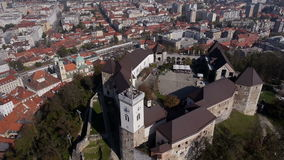 AERIAL: Vertical perspective of Ljubljana Castle with cityscape in the background stock video