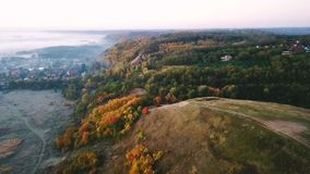 Aerial video footage. Beautiful autumn countryside nature. Hill with road on top and village on background. Top view stock video