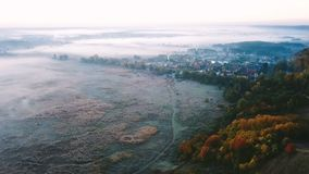Aerial video footage. Foggy autumn sunrise. The cam takin off. On bottom of the field with frozen grass, road and. Village. Video footage. Top view stock video footage