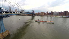 Aerial video footage Manhattan Bridge and boat. Aerial video of a boat traveling under the Manhattan Bridge stock video