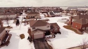 Aerial video of homes in a snow covered suburban neighborhood